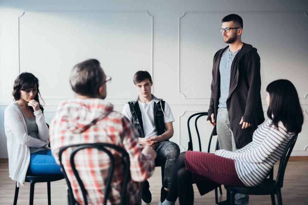 Junger Mann gibt während eines Selbsthilfegruppentreffens zu, dass er Alkoholiker ist