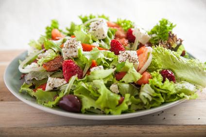 Teller mit frischen Salat auf Holzbrett