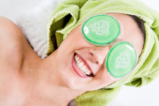 Fröhliche lachende Frau mit Augenpads ihren Augen und Handtuch auf dem Kopf.