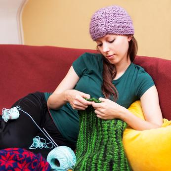 junge Frau mit Wollmütze am stricken