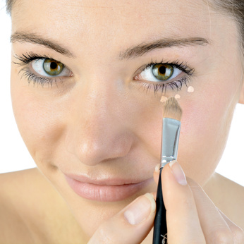 Frau benutzt Make Up gegen Augenringe